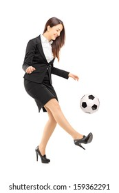 Full length portrait of a businesswoman in high heels kicking a soccer ball isolated on white background