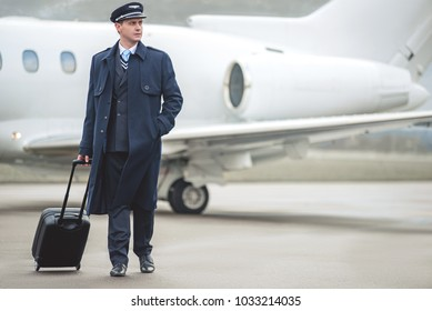 Full length portrait of calm pilot holding baggage while going to aircraft. Journey concept. Copy space