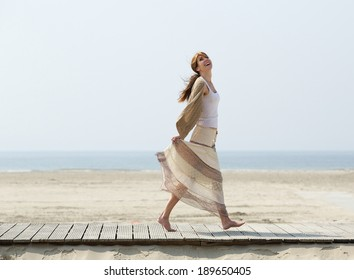 Full length portrait of a carefree middle aged woman walking barefoot at the beach