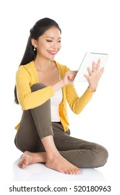 Full length portrait of casual Asian woman sitting on floor smiling and using touch screen tablet pc, isolated on white background.
