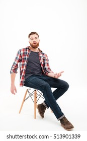 Full length portrait of a casual bearded man talking and gesturing hand while sitting on the chair isolated on white background
