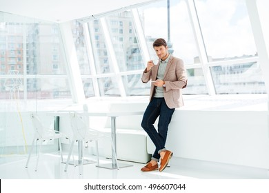 Full length portrait of a casual businessman standing and drinking coffee indoors