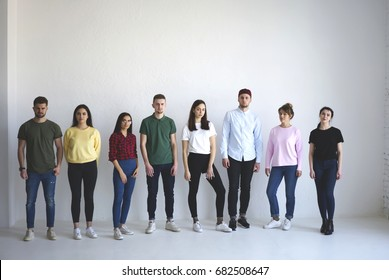 Full length portrait of casual dressed group of young people posing on white wall background with copy space area for your advertise or promotional content. Team, students