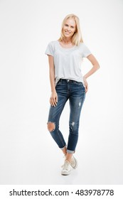 Full length portrait of a casual happy blonde woman standing isolated on a white background
