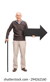 Full length portrait of a casual senior with a cane holding a big black arrow pointing right isolated on white background