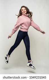 Full length portrait of a casual young woman jumping and looking at camera isolated over white