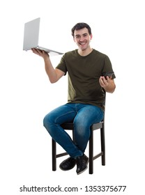 Full length portrait of casual young man sitting on chair holding laptop in one hand and mobile phone in another, comparing gadgets isolated over white background. Technology development concept.