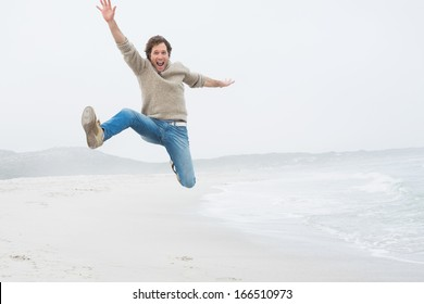Full length portrait of a casual young man jumping at the beach