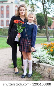 Full length portrait of Caucasian mother and schoolgirl in uniform going back to school, daughter holding flowers