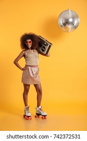 Full length portrait of cheerful african disco woman with hand on her waist wearing in retro clothes standing on roller skates, holding boombox, looking at camera, isolated on yellow background