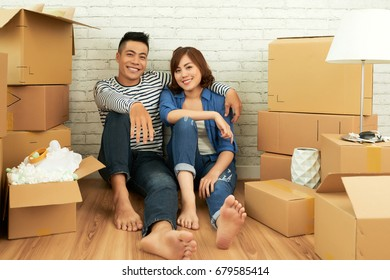 Full length portrait of cheerful Asian couple posing for photography while sitting on floor of living room surrounded with moving boxes