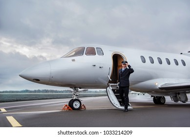 Full length portrait of cheerful aviator leaving stairs of aircraft at airfield. Labor concept. Copy space