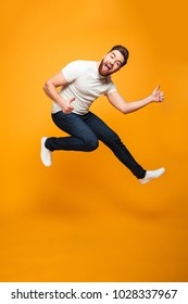 Full length portrait of a cheerful bearded man jumping and showing thumbs up isolated over yellow background