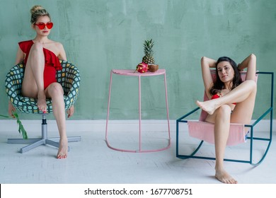 Full length portrait of a cheerful blond girl in red eyeglasses,swimsuit posing in modern chair, her girlfriend in hammock over green mint color background. Quarantine vacation at home, party concept.