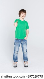 Full length portrait of cheerful boy showing thumb up gesture over white studio background. Happy smiling boy in casual posing on camera. Positive lifestyle and agreement concept. Vertical, copy space