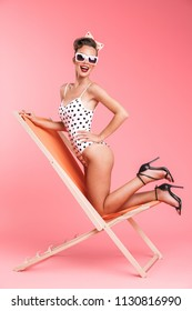 Full length portrait of a cheerful brunette pin-up girl in swimsuit posing on a hammock over pink background