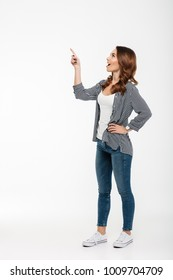 Full length portrait of a cheerful casual girl standing and pointing finger away isolated over white background