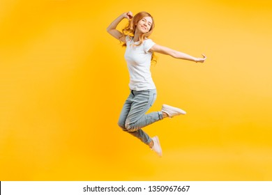 Full length, Portrait of a cheerful enthusiastic girl in a white T-shirt jumping for joy on a yellow background
