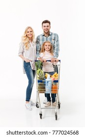 Full length portrait of a cheerful family standing with a shopping trolley full of groceries isolated over white background