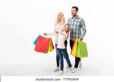Full length portrait of a cheerful family holding paper shopping bags while walking isolated over white background