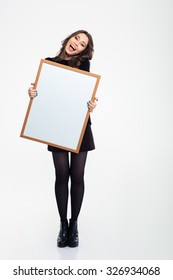 Full length portrait of a cheerful girl holding blank board isolated on a white background