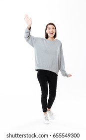 Full length portrait of a cheerful girl waving hand to camera isolated over white background