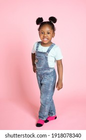 Full length portrait of a cheerful little african girl in trendy casual clothes, with afro hair in two ponytails, isolated over pink background