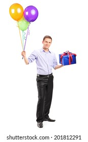 Full length portrait of a cheerful man holding balloons and a present isolated on white background