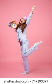 Full length portrait of a cheerful pretty girl dressed in pajamas holding alarm clock while standing and celebrating isolated over pink background