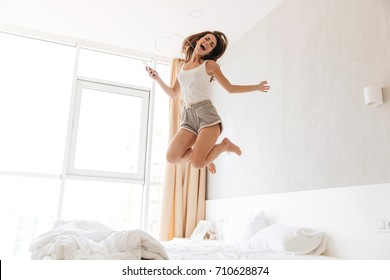 Full length portrait of a cheerful singing woman in earphones listening to music and jumping on bed indoors