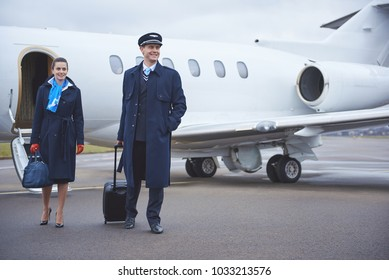 Full length portrait of cheerful stewardess and glad standing near aircraft. Profession concept
