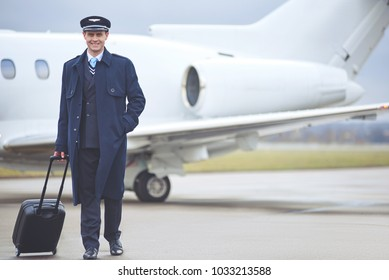 Full length portrait of cheerful young aviator holding luggage while moving from airplane. Trip concept. Copy space
