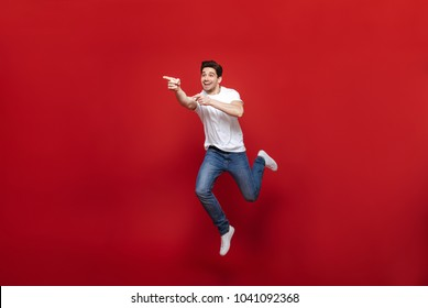 Full length portrait of a cheerful young man in white t-shirt pointing fingers away while celebrating success isolated over red background