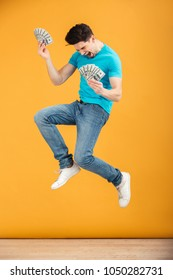 Full length portrait of a cheerful young man in t-shirt holding bunch of money banknotes and celebrating while jumping over yellow background