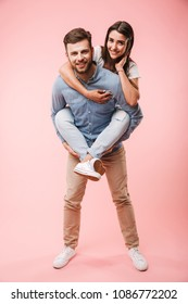Full length portrait of a cheerful young man giving his girlfriend piggyback ride and having fun isolated over pink background