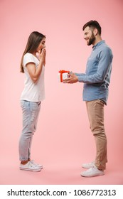 Full length portrait of a cheerful young man giving his girlfriend a present isolated over pink background