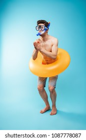 Full length portrait of a cheerful young shirtless man in swim goggles and inflatable ring having fun over blue background