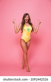 Full length portrait of a cheerful young woman dressed in swimsuit posing while showing peace gesture isolated over pink background