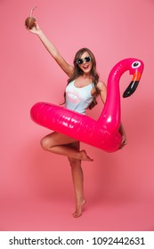 Full length portrait of a cheerful young woman dressed in swimsuit posing with inflatable flamingo and coconut cocktail isolated over pink background