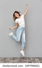 Full length portrait of a cheerful young woman jumping and celebrating over gray background