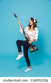 Full length portrait of cheerful young woman 20s listening to music via wireless headphones and having fun with vacuum cleaner isolated over blue background