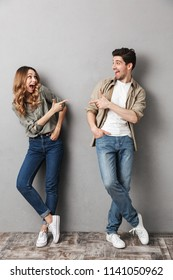 Full length portrait of a cheerful young couple standing together pointing fingers at each other isolated over gray