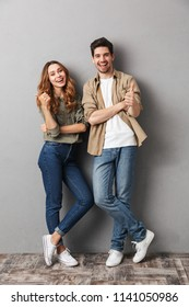 Full length portrait of a cheerful young couple standing together showing thumbs up isolated over gray