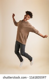 Full length portrait of a cheerful young afro american man dressed in hoodie jumping isolated