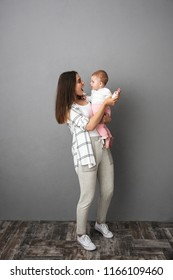 Full length portrait of a cheerful young mother holding her little baby girl over gray background