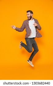 Full length portrait of a cheerful young man wearing casual clothes isolated over yellow background, pointing away at copy space, jumping
