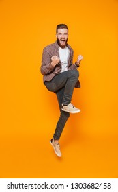 Full length portrait of a cheerful young man wearing casual clothes isolated over yellow background, celebrating success, jump