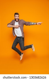 Full length portrait of a cheerful young man wearing casual clothes isolated over yellow background, jumping, pointing away