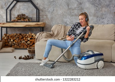 Full length portrait of cheerful young woman 20s listening to music via headphones and having fun with vacuum cleaner in the house.