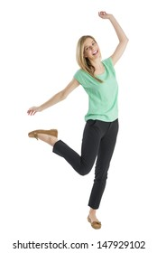 Full length portrait of cheerful young woman standing on one leg with hands raised isolated over white background